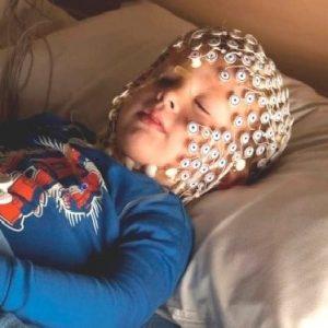 child sleeping while wearing EEG net